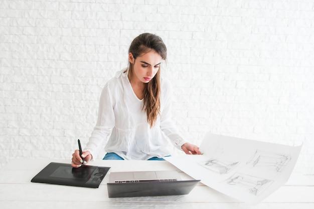 Piękny projektant współpracujący z tabletem graficznym