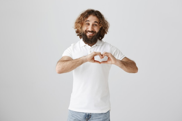 Piękny przystojny mężczyzna z bliskiego wschodu pokazuje gest serca i uśmiecha się