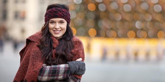 Piękny radosny kobieta portret w mieście. uśmiechnięta dziewczyna jest ubranym ciepłą odzież i kapelusz w zimie lub jesieni
