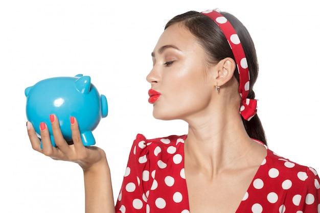 Piękny retro kobieta chwyta prosiątka bank