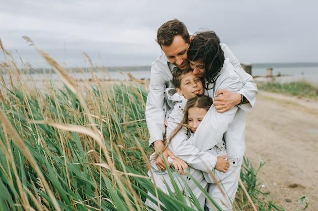 Piękny rodzinny portret ubierający w deszczowu blisko jeziora