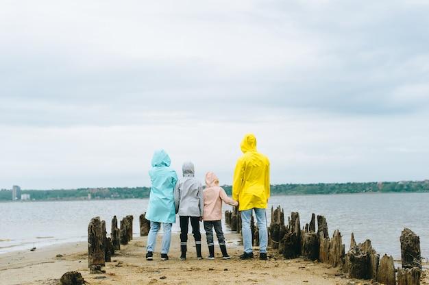 Piękny rodzinny portret ubierający w kolorowym deszczowu blisko jeziora