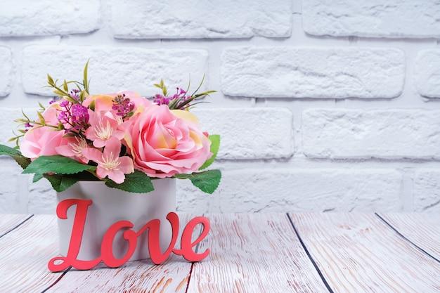 Piękny romantyczny bukiet róż z drewnianym różowym słowem miłość na tle białej cegły ściany. walentynki, koncepcja ślubu.