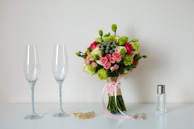 Piękny romantyczny bukiet ślubny z różnych kwiatów, kieliszków do szampana, w błyszczących kamieniach, złotej spinki do włosów, kolczyków. selektywne ustawianie ostrości.