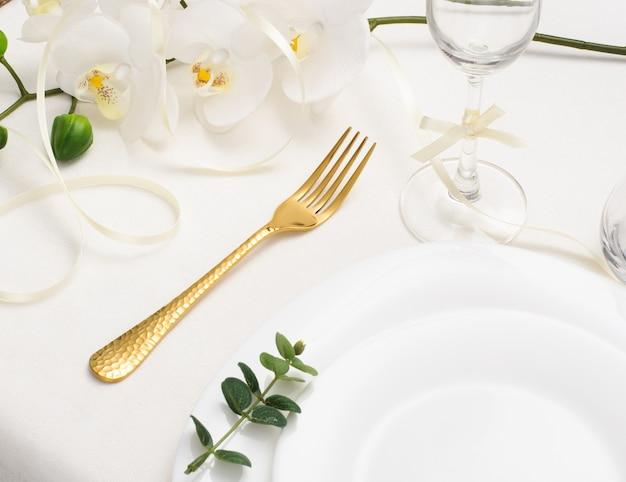 Piękny romantyczny stół ze złotymi sztućcami, orchideą i białym pustym talerzem na białym tle