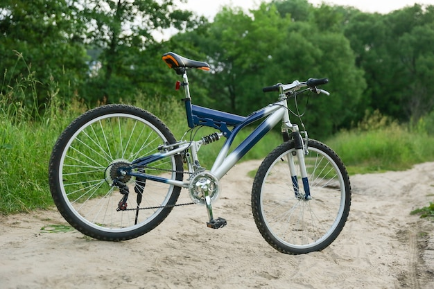 Piękny rower górski jest na piaszczystej drodze