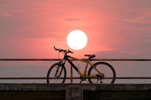 Piękny rower górski na betonowym moście z kolorowym światłem słonecznym.
