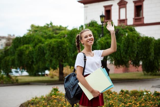 Piękny rozochocony żeński uczeń ono uśmiecha się, powitanie, trzyma falcówki outdoors