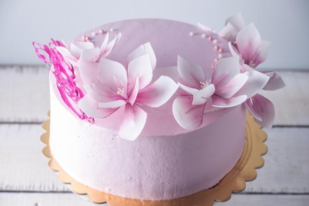 Piękny różowy tort weselny ozdobiony kwiatami