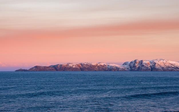 Piękny różowy zachód słońca na oceanie arktycznym. półwysep z ośnieżonymi wzgórzami na horyzoncie. minimalistyczny krajobraz morski. widok panoramiczny.