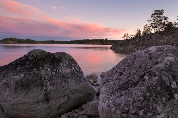 Piękny różowy zachód słońca nad jeziorem ładoga w karelii w rosji w parku narodowym ładoga skerries w lecie. naturalny krajobraz z wodnymi skałami, kamiennymi wyspami.