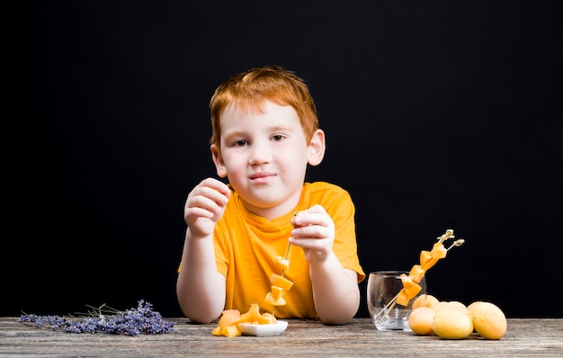Piękny rudowłosy chłopiec z pyszną brzoskwinią w plasterkach