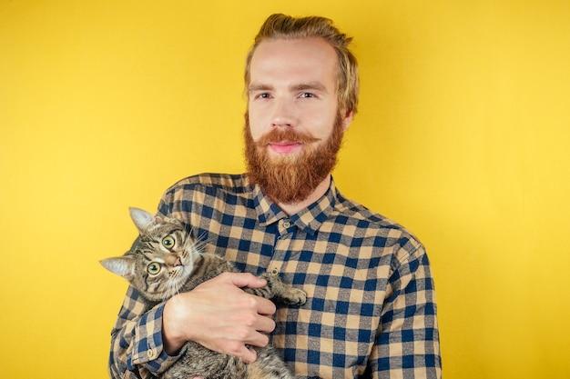 Piękny rudy brodaty wąsy hipster mężczyzna trzyma puszystego kota w rękach