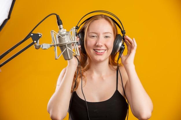Piękny rudzielec kobiety twarzy śpiew z kondensatorowego srebnego mikrofonu otwartym usta spełniania piosenki pozą nad kolor żółty ściany kopii przestrzenią dla twój teksta. spiker radiowy fm.