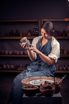 Piękny rzemieślnik demonstruje proces wytwarzania naczyń ceramicznych przy użyciu starej technologii