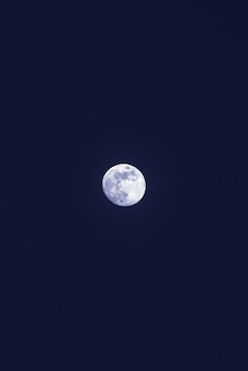 Piękny samotny biały księżyc na ciemnym niebieskim niebie