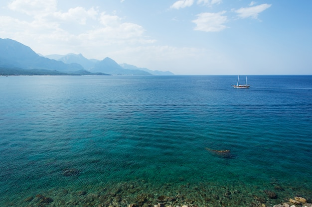 Piękny seascape z morzem, chmurami, górami i jachtem