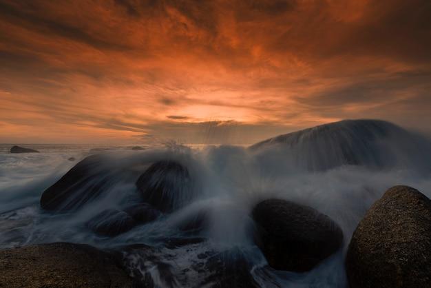 Piękny seascape z morzem i skałą na zmierzchu tle.