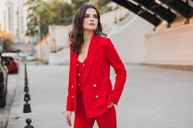 Piękny seksowny bogaty biznes kobieta w czerwonym garniturze spaceru ulicą miasta, trend w modzie wiosna lato