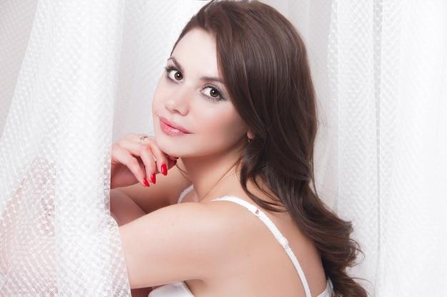 Piękny seksowny brunetki obsiadanie na łóżku