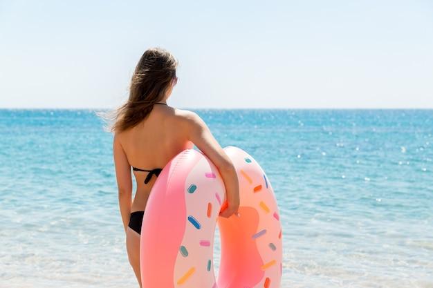 Piękny seksowny ładny szczęśliwy kobieta działa na plaży z różowym gumowym nadmuchiwanym pierścieniem w dłoni. letnie wakacje i koncepcja wakacji.