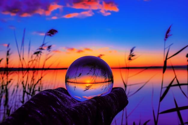 Piękny selektywny strzał ostrości kryształowej kuli odzwierciedlającej zapierający dech w piersiach zachód słońca