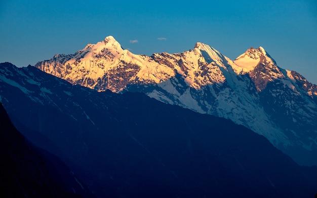 Piękny shining mount gensh z promieniami porannego wschodu słońca, gorkha, nepal.