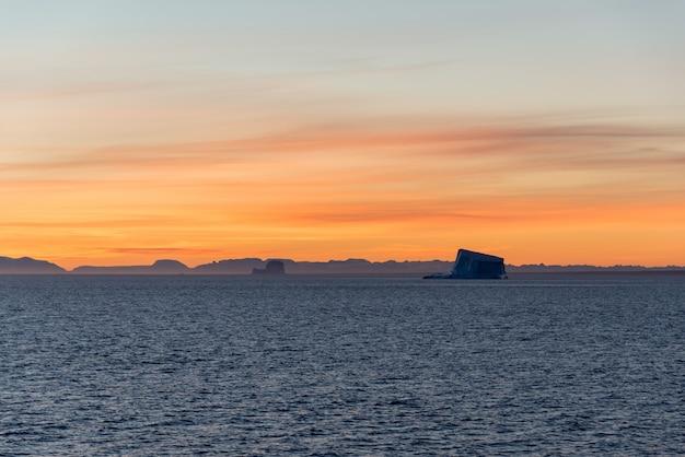 Piękny sinrise na grenlandii. góra lodowa na morzu.