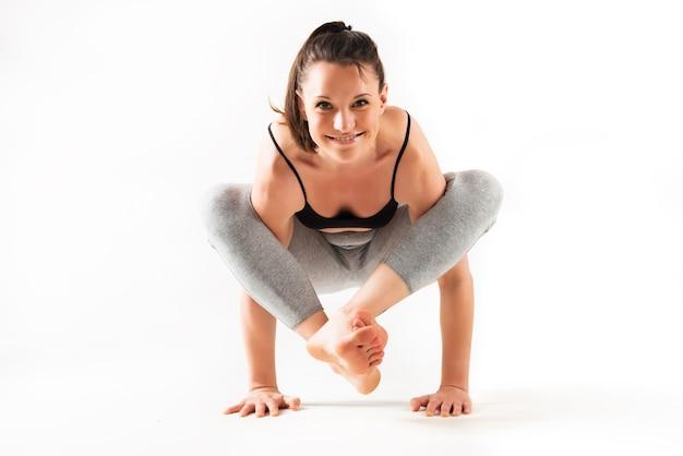 Piękny skoncentrowany młody sportowiec kaukaski kobieta robi złożone zaawansowane asana jogi stojącej na podłodze nad białą ścianą