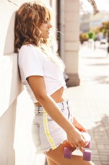 Piękny śliczny blond nastolatka model bez makeup w lato modnisia bielu ubraniach z różowym centu deskorolka pozuje na ulicznym tle
