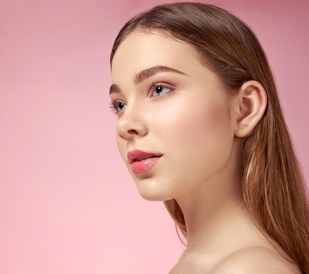 Piękny, śliczny model o perfekcyjnej, zadbanej skórze twarzy na różowo