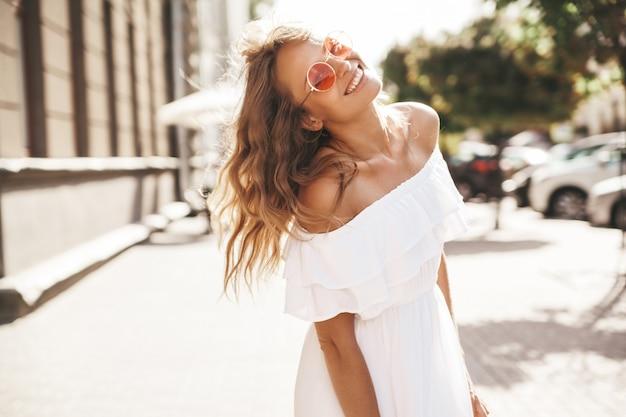 Piękny śliczny uśmiechnięty blond nastolatka model bez makeup w lato modnisia bielu sukni biega na ulicie w okularach przeciwsłonecznych. obróć się