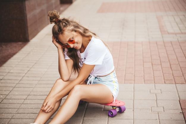 Piękny śliczny uśmiechnięty blond nastolatka model bez makeup w lato modnisia bielu ubraniach siedzi na różowym centu deskorolka na ulicznym tle