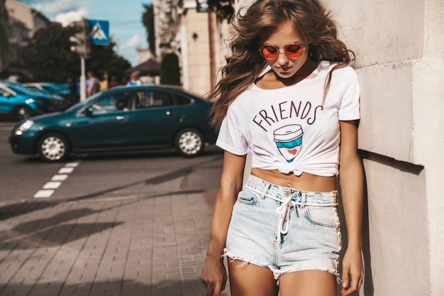 Piękny śliczny uśmiechnięty blond nastolatka model bez makeup w lato modnisia bielu ubraniach z różowym centu deskorolka pozuje na ulicznym tle
