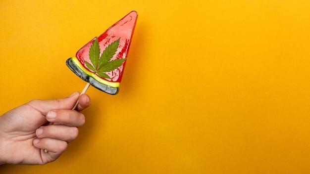 Piękny słodki czerwony lizak z marihuaną w ręku na żółtym tle, cukierki z konopiami.