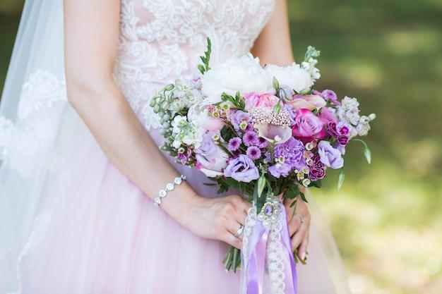 Piękny ślub kolorowy bukiet z różnych kwiatów w rękach panny młodej. letni bukiet ślubny