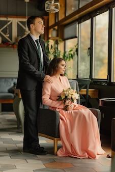 Piękny ślub, mąż i żona, panna młoda i pan młody w poddaszu wnętrze w pobliżu okna. para nowożeńców w miłości. pan młody przytulić pannę młodą.