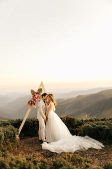 Piękny ślub w górach, zakochana para ślubna trzymać się za ręce i uśmiechać.