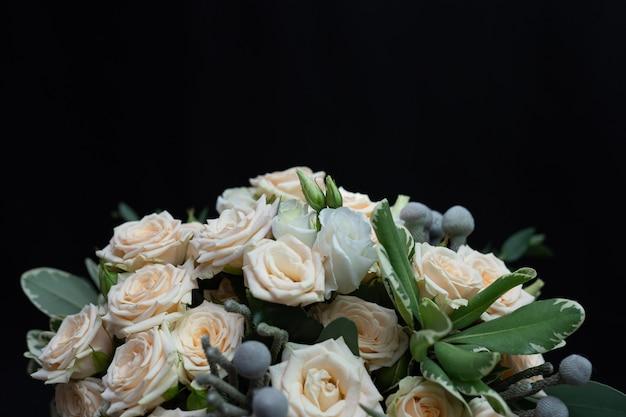 Piękny ślubny bukiet krzaczastej róży kremowej, eukaliptusa, brunei, pittosporum i lisianthus na czarnej ścianie.
