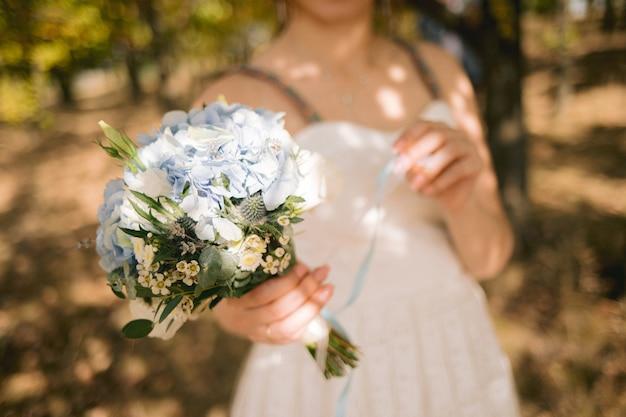 Piękny ślubny bukiet kwiatów w rękach panny młodej