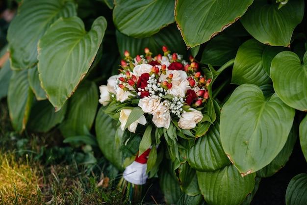 Piękny ślubny bukiet na zielonej trawie na letnim dniu.