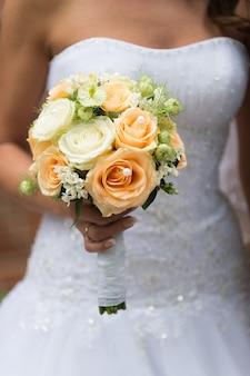 Piękny ślubny bukiet róż w rękach panny młodej