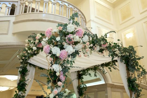 Piękny ślubny huppah ozdobiony świeżymi świeżymi kwiatami