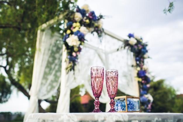 Piękny ślubny łuk i stół z okularami w przyrodzie. dekoracje ślubne.