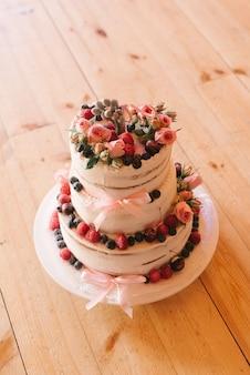 Piękny ślubny tort z świeżymi jagodami na drewnianym stole