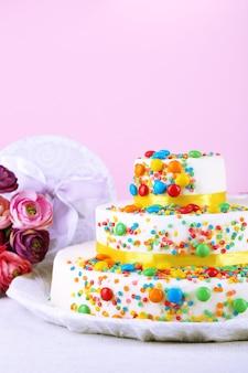 Piękny smaczny tort urodzinowy i prezenty na kolorowym tle