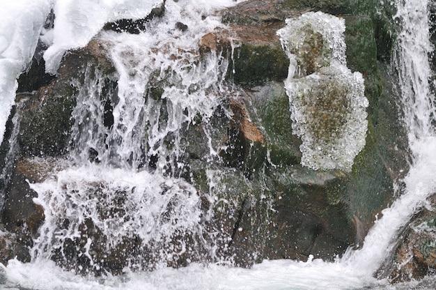 Piękny śnieżny wodospad płynący w górach