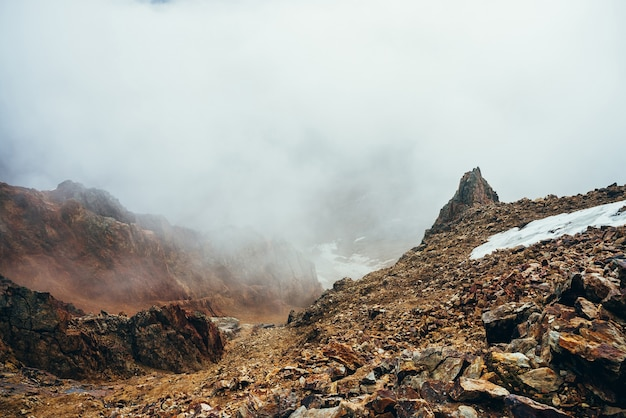Piękny spiczasty klif na wysokiej skalistej krawędzi ze śniegiem wśród grubych niskich chmur. klimatyczny, minimalistyczny krajobraz alpejski. spiczasty kamień w pobliżu przepaści w wielkiej chmurze. cudowna góralska sceneria.