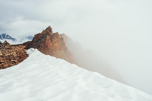 Piękny spiczasty skalisty szczyt na górze ze śniegiem wśród grubych niskich chmur. klimatyczny, minimalistyczny krajobraz alpejski. ostry skalisty szczyt góry ponad gęstymi chmurami w otchłani. cudowna góralska sceneria.
