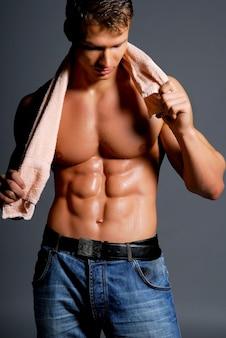 Piękny sportowiec trzymając ręcznik. obraz sportu.